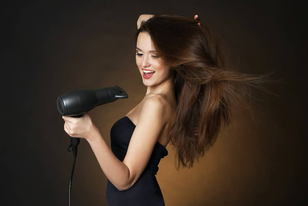 Beautiful young woman with long hair holding blow dryer / hair dryer.
